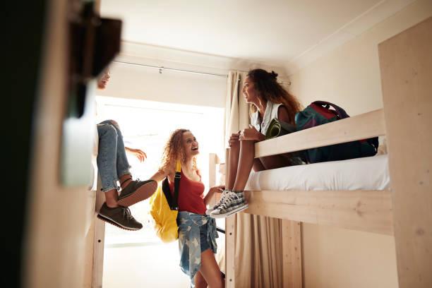 Dortoir d'une auberge de jeunesse avec trois adolescentes sur des lits à étage